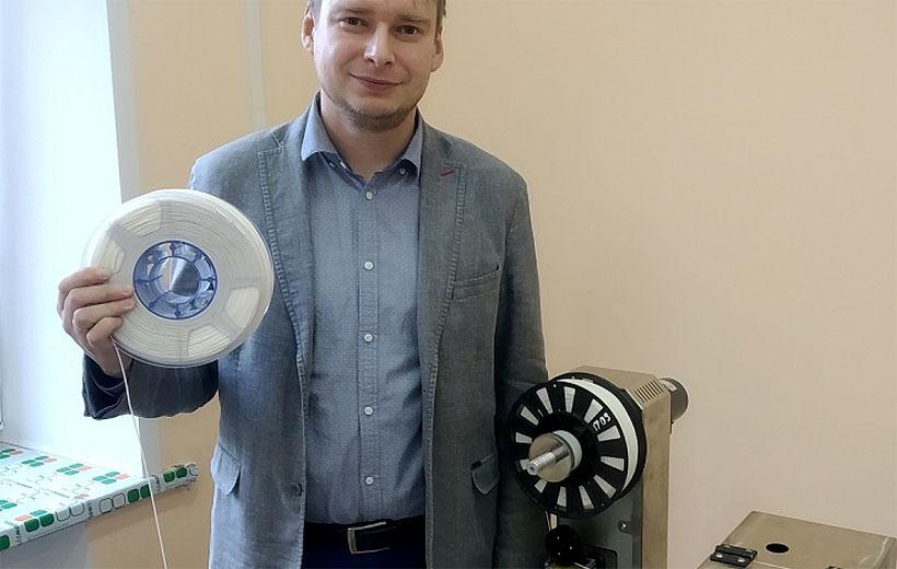 Сотрудник ЯГТУ с образцом полимерной нити для 3D-печати, полученной на лабораторной экструзионной линии